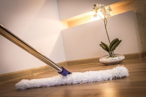 modern white mop cleaning wooden floor in house - illustrate the importance of clean environment for meditation